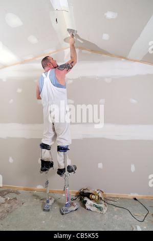 Man plastering wall on stilts - Stock Photo