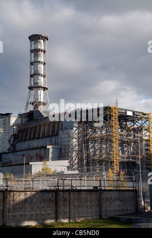 Reactor Number 4 at Chernobyl, encased in its old sarcophagus with the new one being constructed by its side, Ukraine - Stock Photo