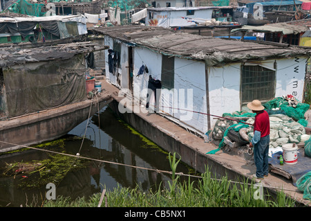 China, Jiangsu, Qidong, Man in a red shirt and straw hat fishing with a rod and line off his boat moored in a canal. - Stock Photo