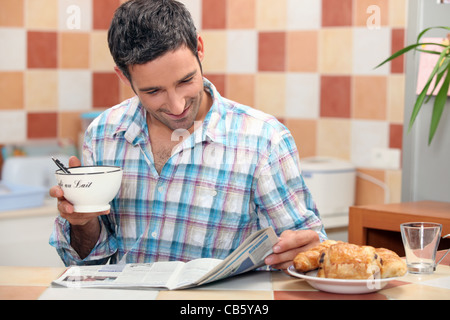Man reading a magazine at the breakfast table - Stock Photo