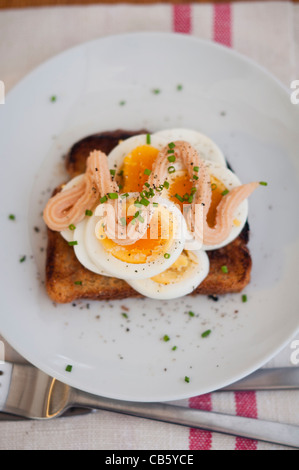 Classic Swedish open faced sandwich of sliced boiled egg topped with Kalle's kaviar and sprinkled with chopped chives. - Stock Photo