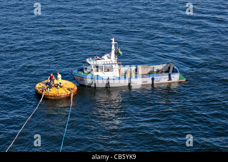Stockholm;anchor;ropes;release;two;men;boat;sea; Capital of Sweden;Scandinavia;Europe - Stock Photo