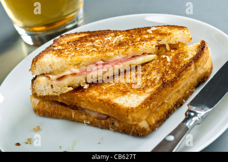 Classic French toasted cheese and ham sandwich snack, Croque Monsieur with glass of beer - Stock Photo