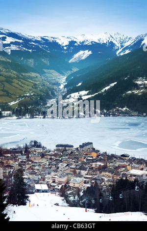Aerial view down on Zell Am See (Austria, Alpes) town, frozen lake, ski resort and mountains in fog. - Stock Photo