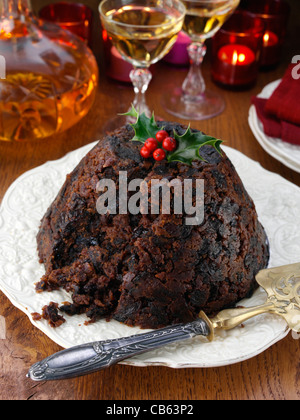 Whole Xmas pudding with brandy decanter and glasses in the background - Stock Photo