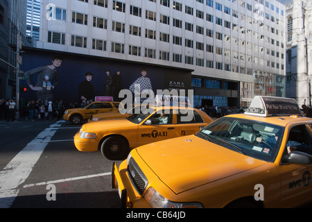 Taxis wait at a traffic light on Fifth Avenue in front of a construction shed promoting a new Zara store in New - Stock Photo
