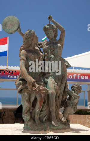 Bronze state of grape pickers outside cafe restaurant in Jaffa Israel - Stock Photo