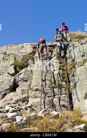 Hikers descend the permanent  ladders on the trail down from Lac Blanc and the Lac de Cheserys in the Chamonix Valley - Stock Photo
