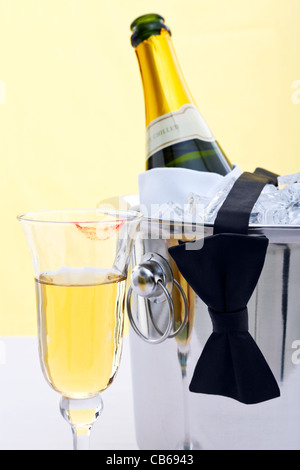 Photo of a bottle of chilled Champagne in an ice bucket with a black bow tie draped over it and a glass with a red - Stock Photo