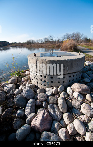 A perforated concrete pipe forms part of a stormwater management system in a suburban pond. - Stock Photo