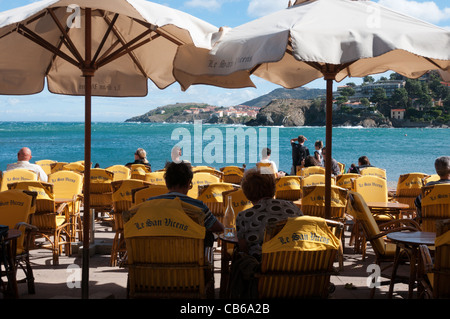Tourists sitting and relaxing under sun umbrellas at a beach cafe in Collioure, southern France - Stock Photo