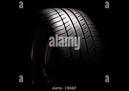 Modern high-performance sport summer tyre isolated on a black background. Vertical composition. - Stock Photo
