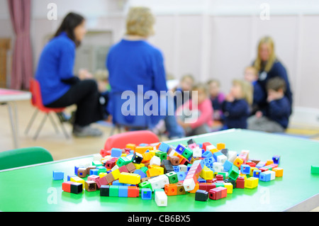Preschool group UK Children and teachers with activity in foreground. - Stock Photo