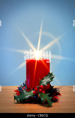 Photo of a Christmas candle and holly with starburst, the star from the flame was created in camera using a filter.