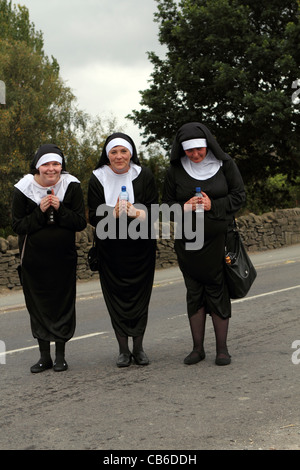 Three women dressed up in  nun costumes during Barlow Carnival parade  in Derbyshire East Midlands England UK - Stock Photo