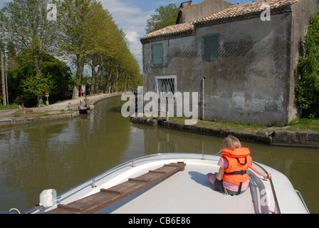 Photographer's daughter sitting on the bow deck of a houseboat travelling the Canal du Midi, passing a lock near - Stock Photo