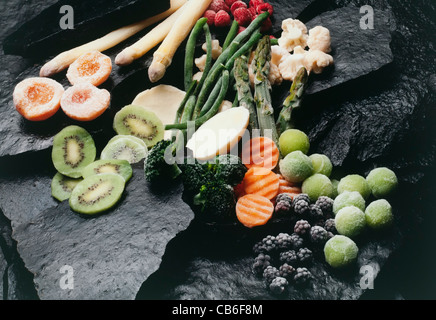 frozen fruits and vegetables on black stones - Stock Photo