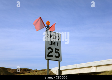 Traffic sign showing the maximum speed limit of 25 miles per hour - Stock Photo