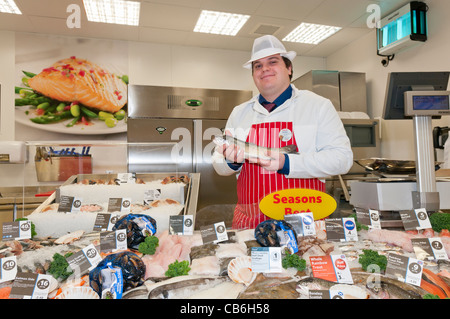 Man holds a rainbow trout at the fish counter in a Tesco Store - Stock Photo