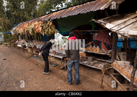 India, Nagaland, Mon, western tourist and guide looking at local produce for sale on roadside stalls - Stock Photo