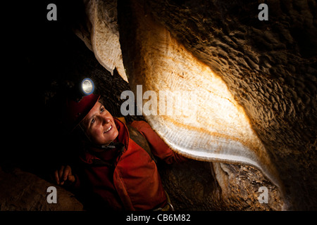 Female caver with stalactite curtain in French cave - Stock Photo