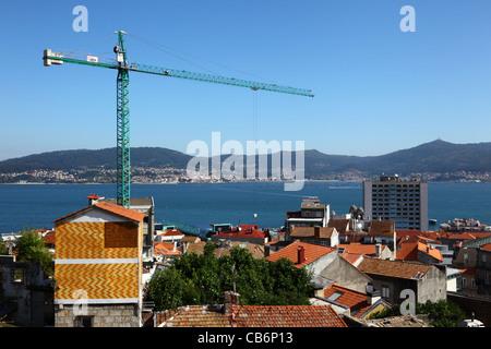 Crane and houses , Ria de Vigo and village of Cangas in background, Vigo , Galicia , Spain - Stock Photo