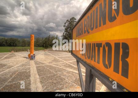 Orange sign pointing to the equator line at zero degrees - Stock Photo