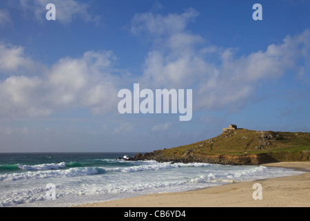 Surf in rough seas off Porthmeor beach in evening sun, St Nicholas chapel on the island, St Ives, Cornwall, Southwest - Stock Photo