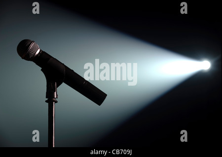 Spot lit microphone and stand on an empty stage - Stock Photo