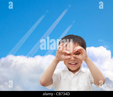 happy boy watching airplane flying through the sky over the cloud - Stock Photo