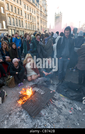 Protestors sitting around burning placards on Whitehall, Palace of Westminster behind, Student Demonstration, London, - Stock Photo