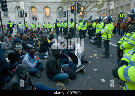 Standoff between police in riot gear and seated protestors on Whitehall, Day X Student Demonstration, London, England - Stock Photo