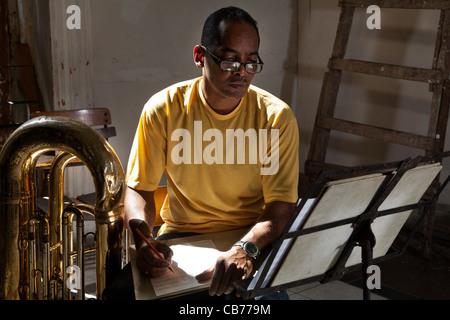 A tuba player taking notes in the Asociacion Rosalia de Castro, Havana (La Habana), Cuba