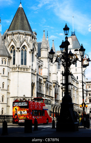 Tourist open-topped red bus passes the Royal Courts of Justice on a sunny day in London UK. - Stock Photo