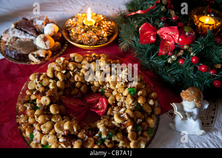 Traditional Christmas cakes arrayed on a table together with period decorations in a household in Gozo in Malta. - Stock Photo
