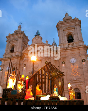 A Christmas tree and crib are put up for Christmas festivities outside the parish church of Xaghra town in Gozo - Stock Photo