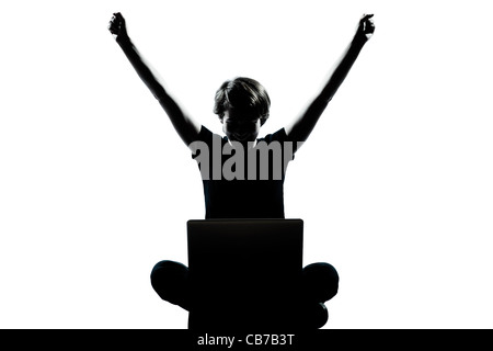 one caucasian young teenager silhouette boy  girl computer computing laptop happy success full length in studio - Stock Photo