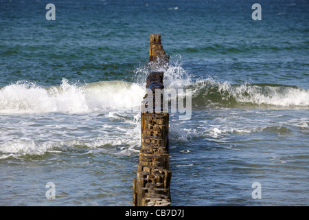 Groynes in the surf on the German Baltic coast - Stock Photo
