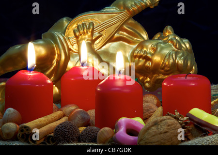 Advent wreath with three burning candles and a golden angel in the background - Stock Photo
