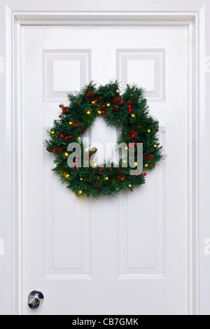 Photo of a Christmas wreath with lights hanging on a white front door. - Stock Photo