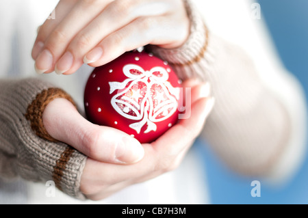 young woman against blue background wearing winter clothes holding red christmas ball toy in her hands - Stock Photo