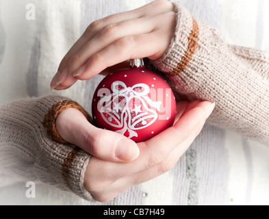 young woman wearing winter clothes holding red christmas ball toy in her hands - Stock Photo