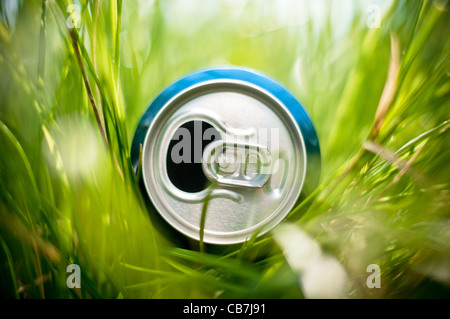 opened blue aluminum can (bottle) laying in green grass, very shallow depth of field - Stock Photo