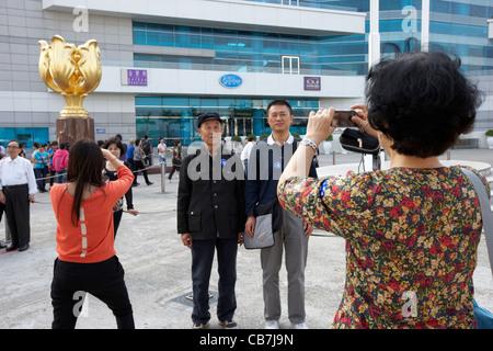 mainland chinese tourists taking photos in golden bauhinia square hong kong island, hksar, china - Stock Photo