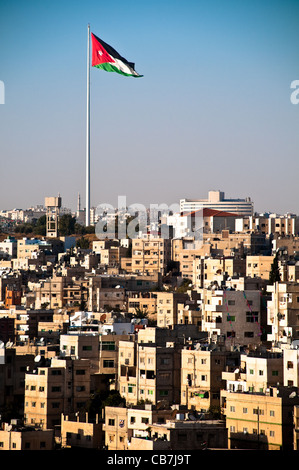 view of city of Amman with giant jordanian flag and blue sky in background - Stock Photo