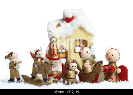Christmas Decorations with a ceramic wind light and small wooden figure isolated on white background - Stock Photo