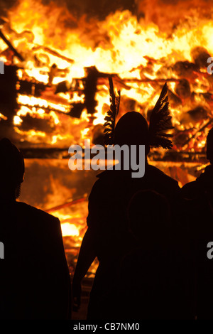 Silhouetted 'Vikings' against a burning Viking Galley at the Up Helly Aa festival in Lerwick on the Shetland Islands. - Stock Photo