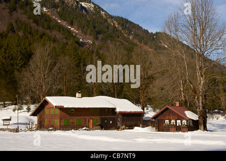 Snow covered wooden farmhouse in the Allgau Alps in winter - Stock Photo