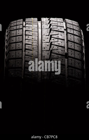 Brand new car tyre. Vertical composition. - Stock Photo