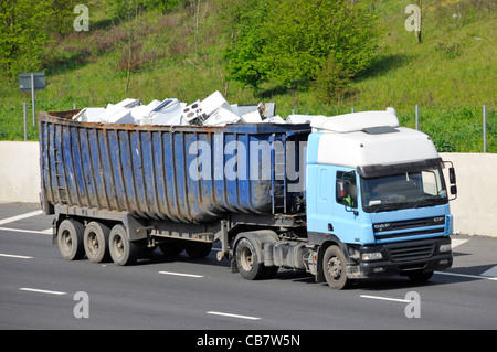 Unmarked scrap metal hgv lorry truck with articulated trailer loaded with recycling white goods domestic kitchen - Stock Photo